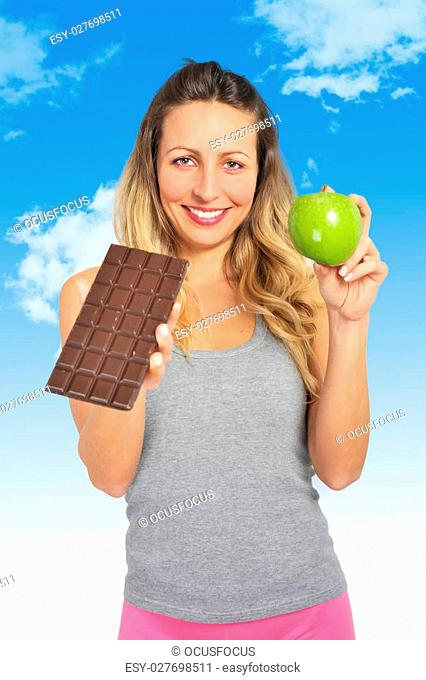 young attractive sport woman holding apple and chocolate bar in her hands in healthy fruit versus sweet junk food dilemma in fitness