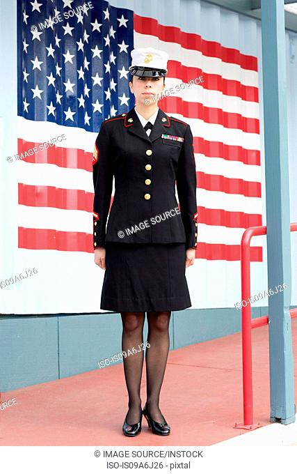 Servicewoman in dress blues by US flag