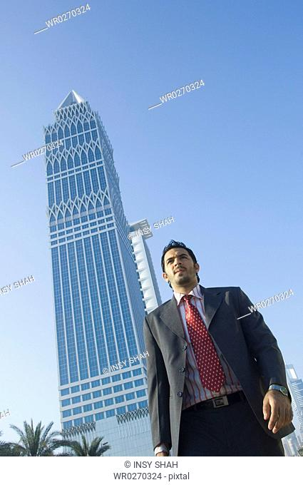 Young man walking outdoors with skyscrapers in the background