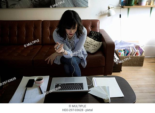 Female architect working at laptop in living room