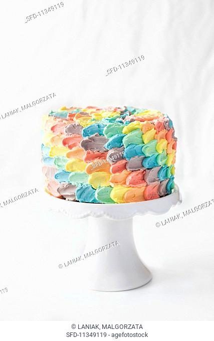A rainbow petal birthday cake on a cake stand