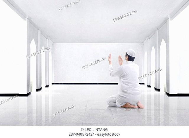 Back view of asian muslim man kneeling and praying to god in the mosque