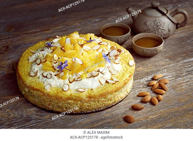 Healthy home-made flourless, sugar-free, dairy-free vegan cake made of almond flour, oranges and coconut, artistic food still life with a clay teapot on rustic...
