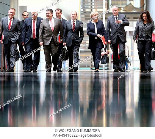 The chairman of the Social Democratic Party (SPD), Sigmar Gabriel (C) arrives together with (L-R) parliamentary executive Thomas Oppermann
