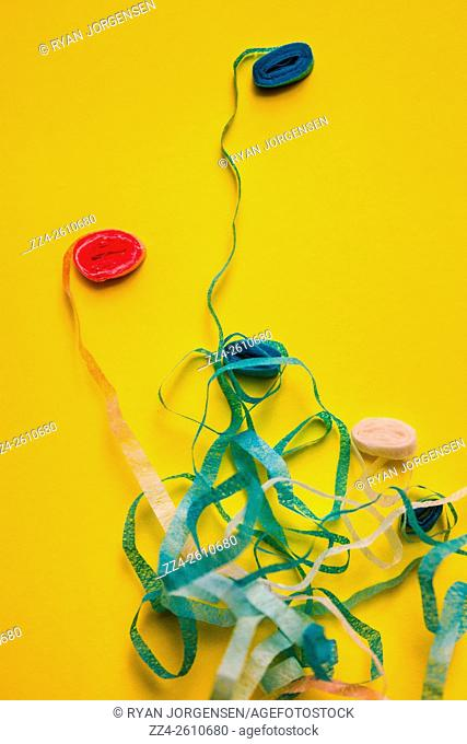 Messy birthday still-life of colorful streamers on yellow background. Unravelling celebrations