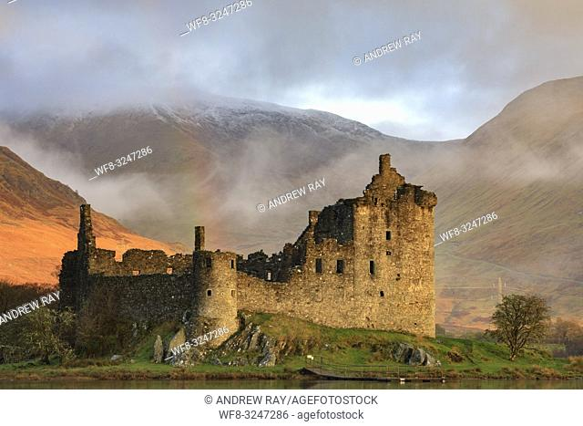 Warm early morning sunlight on the face of Kilchurn Castle on Loch Awe in Scotland. The image was captured using a telephoto lens on an atmospheric morning in...
