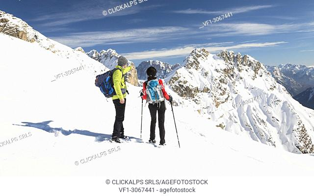 Two hikers are looking at the dolomitic landscape with the Monte Civetta in the background, Trento province, Trentino Alto Adige, Italy