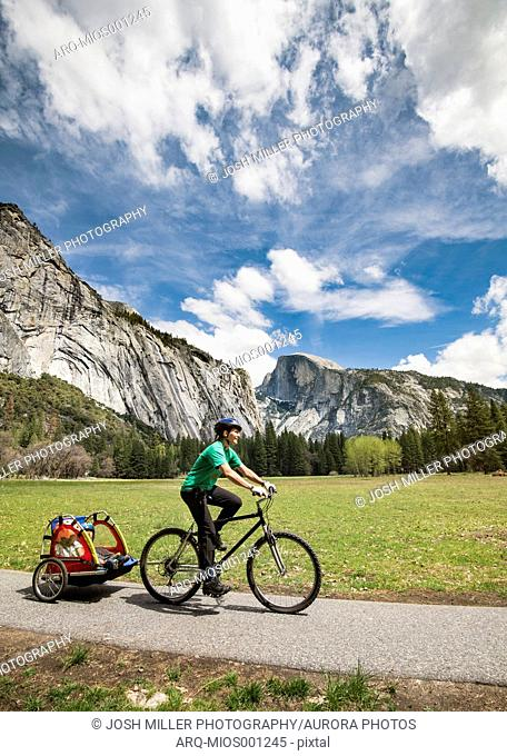 Woman bike riding with kids, Half Dome in backgound