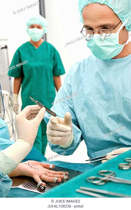 Nurse handing doctor surgical knife in operating room