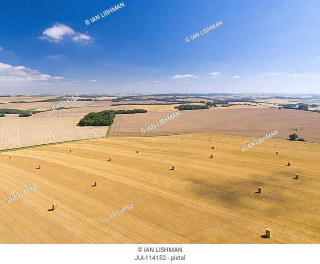 Aerial View Of Harvested Farm Fields With Bales Of Straw