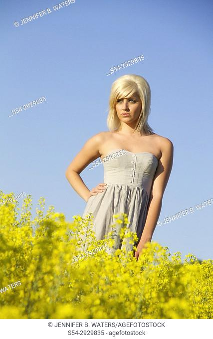 A young woman looking at a canola field in Spokane County, Washington, USA