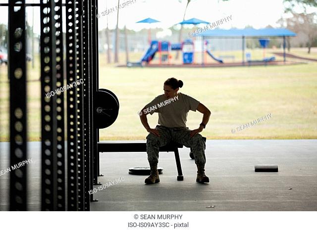 Silhouetted female soldier barbell training at air force military base