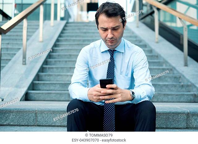 Sad depressed businessman reading bad message on smartphone