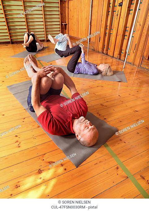 Older people practicing yoga in studio