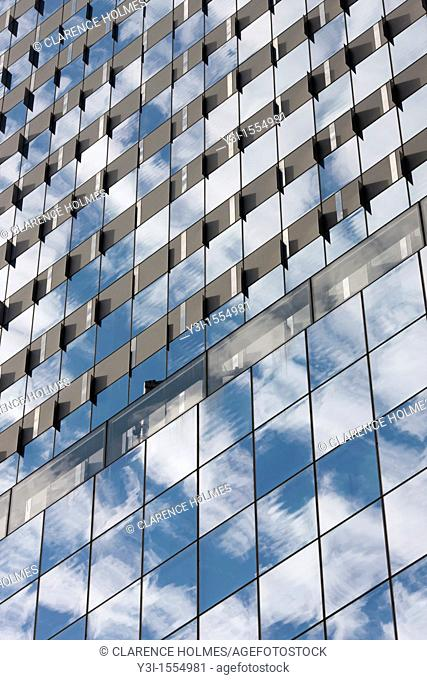 The sky and clouds reflected in the windows of building facades in New York City, USA