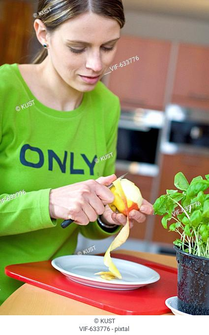 junge Frau schaelt einen Apfel - Nieder÷sterreich, Ísterreich, 14/02/2008