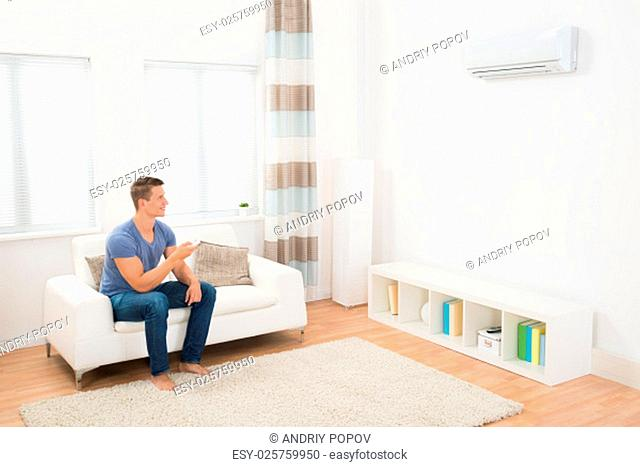 Young Man On Sofa Operating Air Conditioner With Remote Control