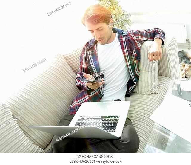 young man with laptop and smartphone sitting on sofa in living room. photo with copy space