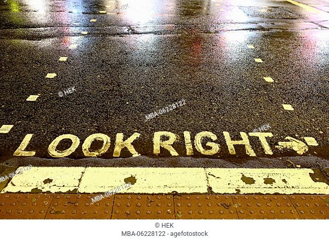 Road marking on a rainy road, look right