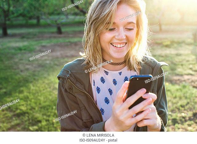 Head and shoulders of young woman using smartphone looking down smiling