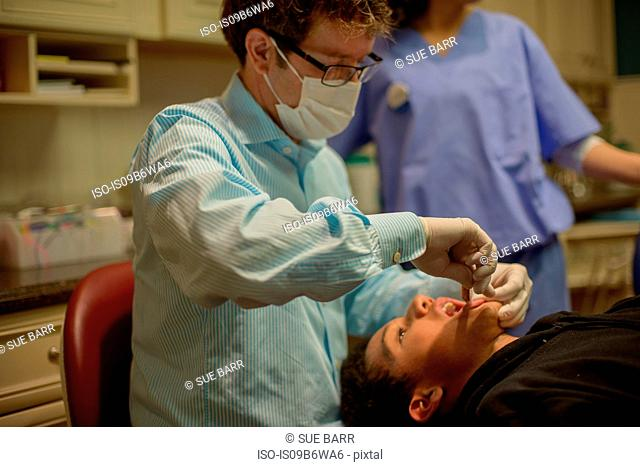 Male orthodontist treating teenage boy in dentist office