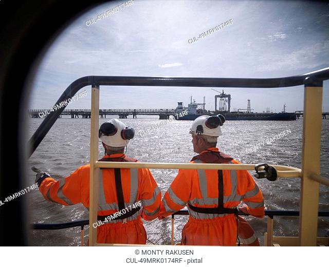 Tugboat workers standing on deck