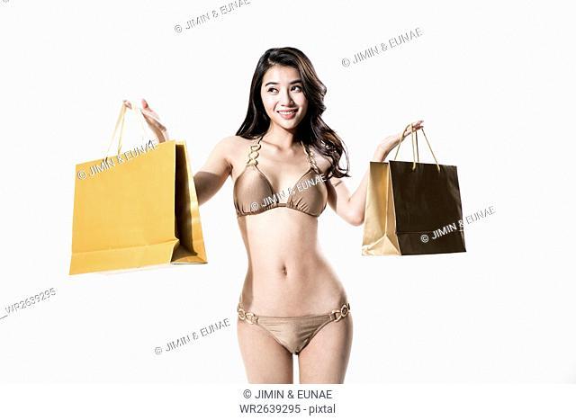 Young smiling woman in bikini holding shopping bags