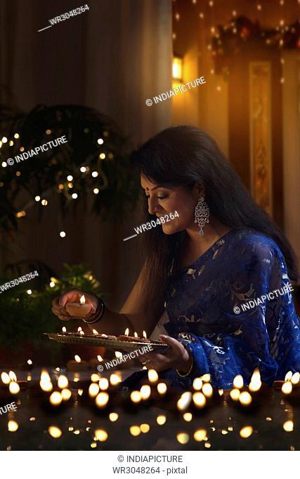Beautiful woman in traditional sari arranging oil lamp during diwali festival