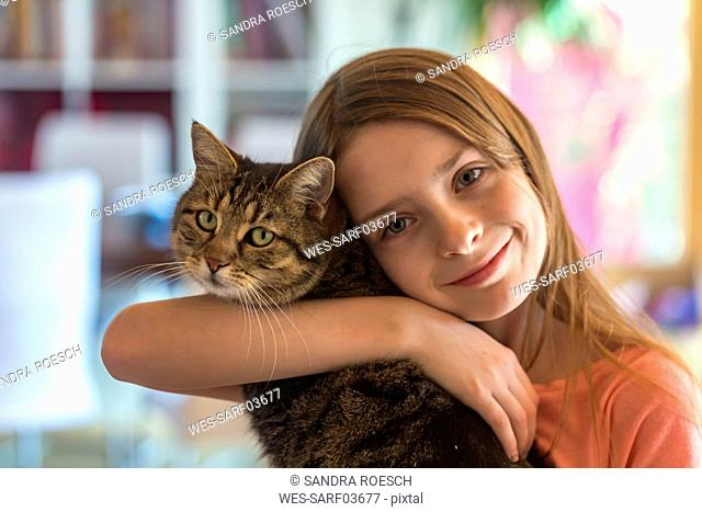 Portrait of smiling girl with her tabby cat