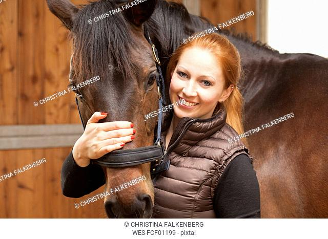 Portrait of happy young woman with her horse