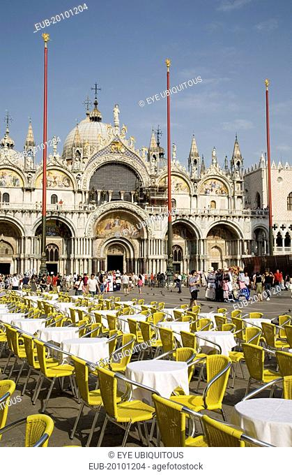 Centro Storico St. Marks Square Cafe tables prepared for customers in early morning sunshine with facade of Basilica di San Marco behind