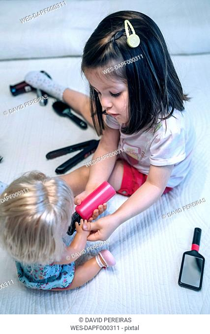 Girl playing with doll and hairdressing toys