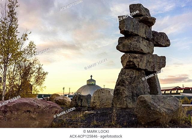 an Inukshuk and the Our Lady of Victory Church, Inuvik, Northwest Territories, Canada