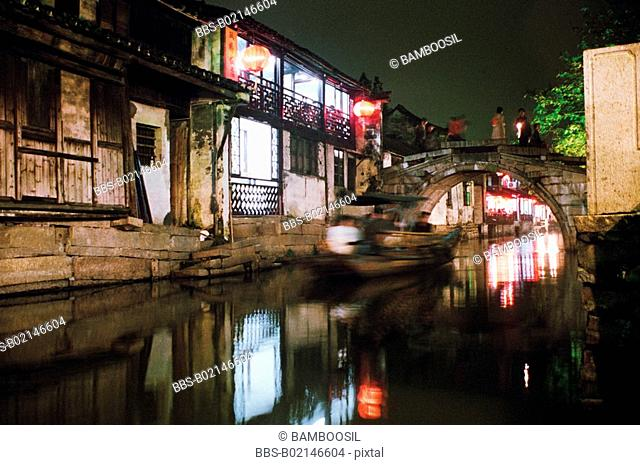 Boat moving in lake under bridge at night, Zhouzhuang Town, Kunshan City, Jiangsu Province, People's Republic of China