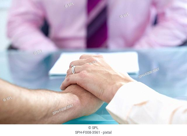 MODEL RELEASED. Consultation. Couple talking to a doctor