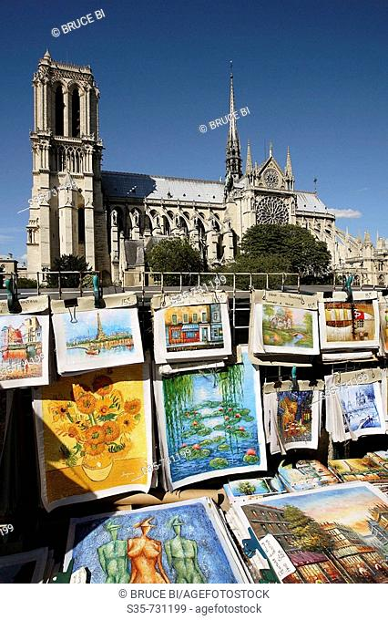 France. Paris. Posters for sale on the roadside with Notre-Dame Cathedral in the background