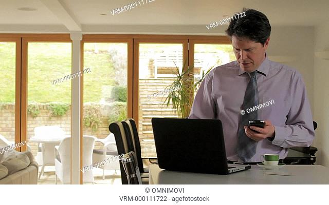Mature man using smart phone and laptop on kitchen counter