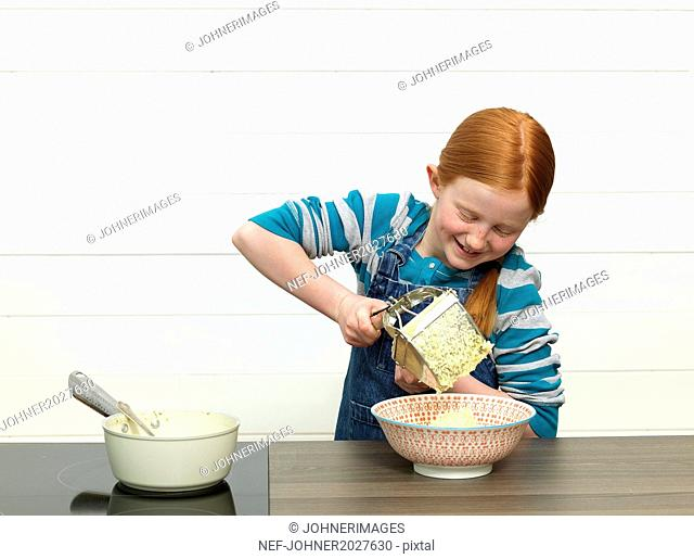 Girl ricing potato for mash