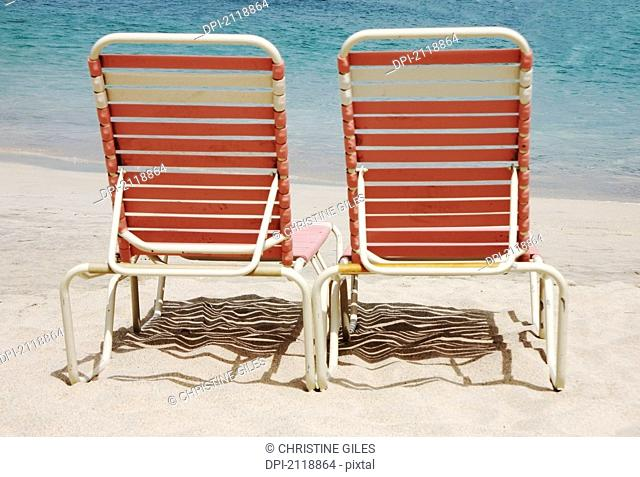 Two pink lounge chairs on a white sand beach, cane garden bay tortula british virgin island