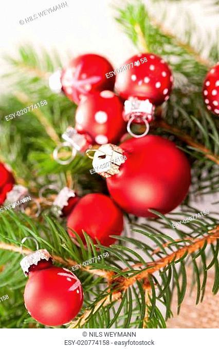 Schöne rote Weihnachtskugeln mit kleinen Weißen Punkten mit grünen Tannenzweigen