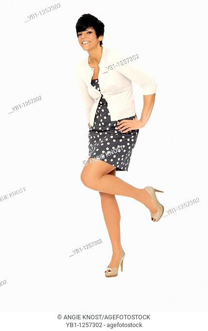 Attractive, happy woman, standing, smiling and kicking up one foot