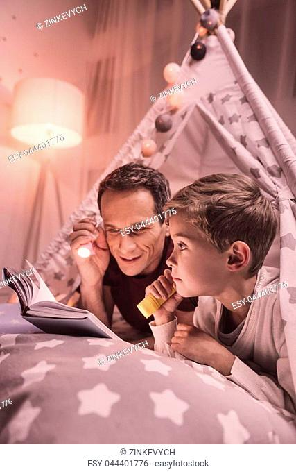 Magical atmosphere. Happy positive nice man holding a flash light and smiling while reading a book together with his son