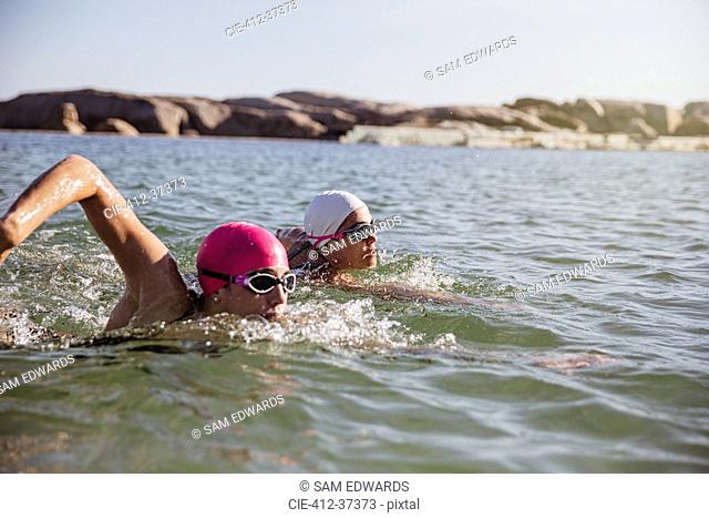 Determined, focused female open water swimmers swimming in sunny ocean