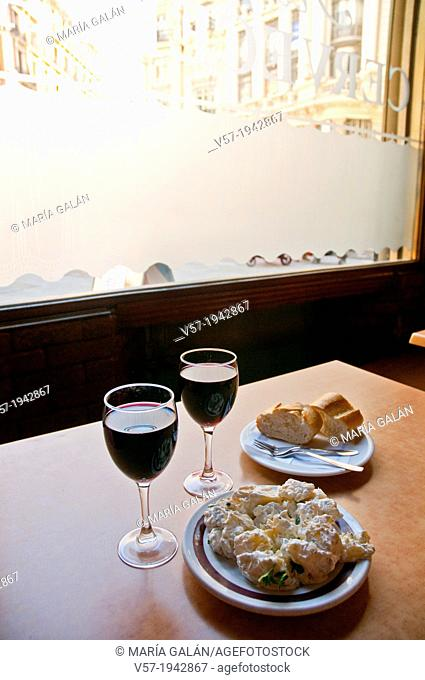 Spanish appetizer:alioli potatoes serving and two glasses of wine. Madrid, Spain