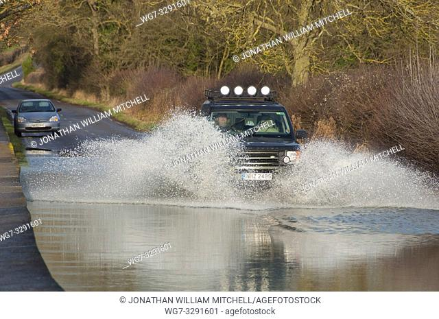 FELMERSHAM, ENGLAND, UK - Jan 10, 2014: A motorist drives his 4x4 Land Rover through floodwaters on a road in Felmersham, Bedfordshire, England, UK