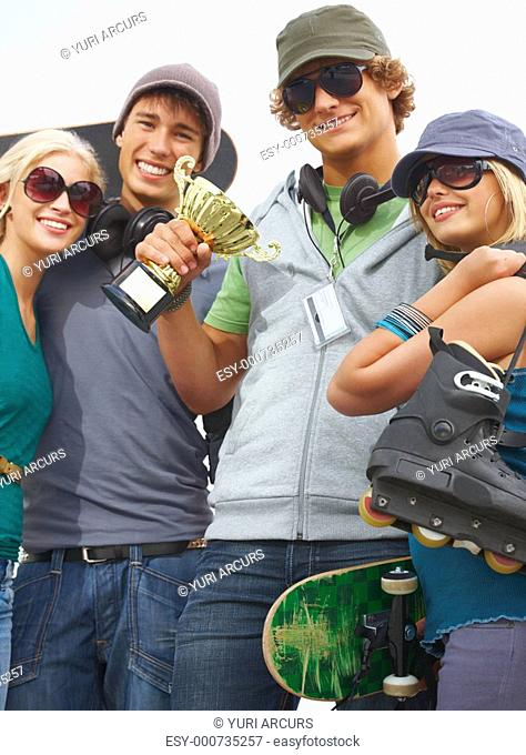 Group of happy friends standing together, man holding prize