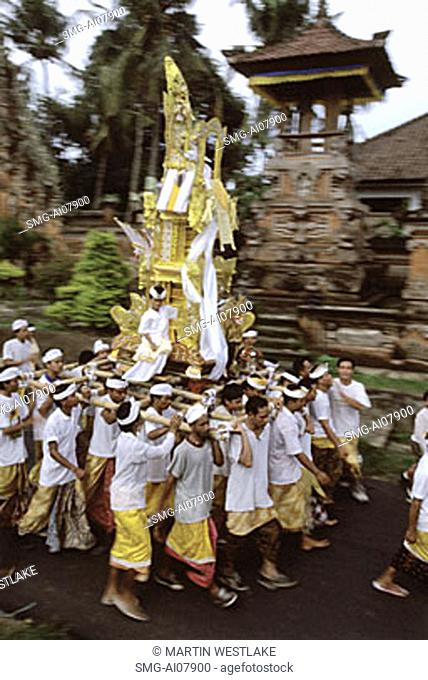 Indonesia, Bali, Gianyar, Pengastian ceremony, men carrying ceremonial tower to sea. (grainy)