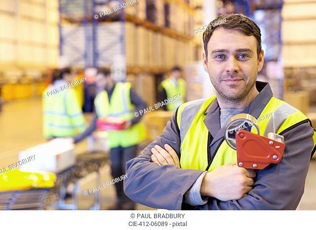 Worker holding tape dispenser in warehouse