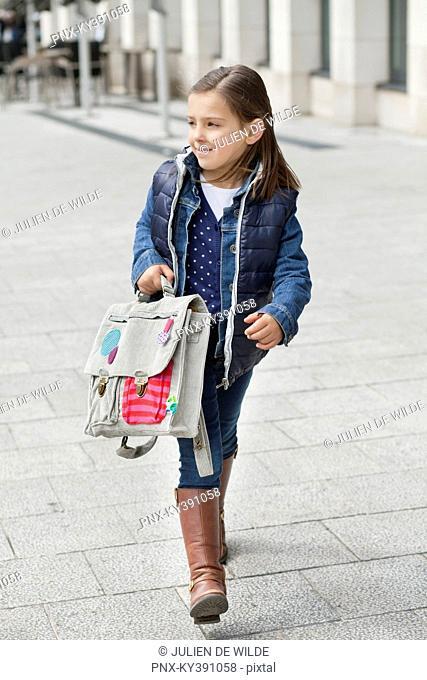 Schoolgirl carrying her schoolbag
