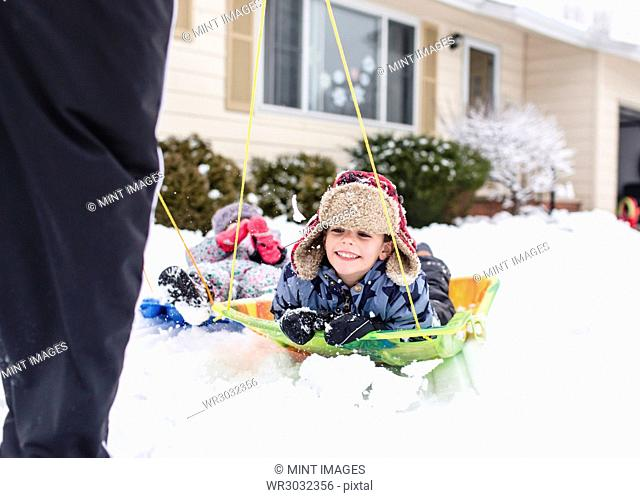 Smiling boy wearing furry hat and girl lying on sledges in the snow